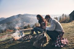 Resting together. Beautiful young couple having morning coffee w. Hile sitting by the campfire in mountains Stock Image