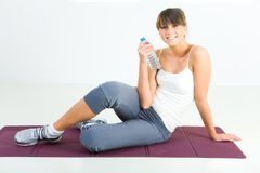 Resting after training. Young woman dressed sportswear sitting on mat and holding water bottle. She's smiling and looking at camera. Front view stock images
