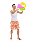 Resting on vacation man playing with beach ball. Resting on vacation happy young man playing with beach ball isolated on white Royalty Free Stock Photography