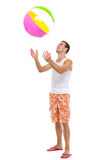 Resting on vacation man throwing beach ball up Royalty Free Stock Image