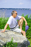 Resting walker. A man resting on a boulder at the beach Stock Image