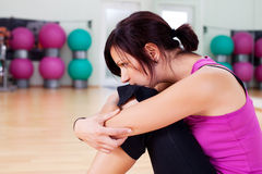 Resting woman. Woman resting head on her knees after workout in gym Royalty Free Stock Photos