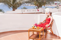 Resting  woman is sitting and dreamingin a chair at the terrace. Stock Photography