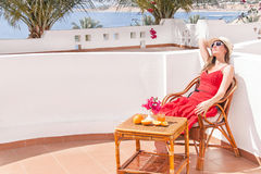 Resting  woman is sitting and dreamingin a chair at the terrace. Royalty Free Stock Photo