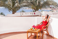 Resting  woman is sitting and dreamingin a chair at the terrace. Stock Photo