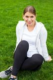 Resting after workout in the park. Smiling young woman resting on the grass after a workout session in the park Stock Photography