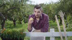 Resting young farmer eating tasty apple standing in the foreground, the summer garden in the background. The man resting. After work. Rural lifestyle stock video footage