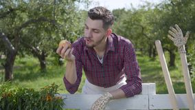 Resting young man eating tasty apple standing in the foreground, the summer garden in the background. The man resting. After work. Rural lifestyle stock footage