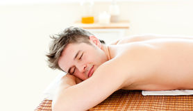 Resting young man lying on a massage table Stock Photos