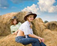 Restings delle ragazze dell'azienda agricola su fieno Immagine Stock Libera da Diritti