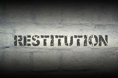 Restitution WORD GR. Restitution stencil print on the grunge white brick wall Stock Photography