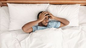 Restless african american man waking up with headache. Lying in bed early in morning, top view royalty free stock image