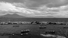 Restless Bay of Naples overlooking the Vesuvius and the beautiful boats in the foreground. Black and white Stock Images