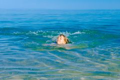 Excited child girl jumping with widespread hands in shallow sea. Restless beautiful cheerfully child is having fun and jumping out with widespread hands in sea royalty free stock images