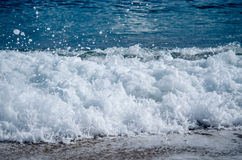Restless foamy blue wave is coming at Mediterranean sea. Shot made on barcelona city beach Stock Photography