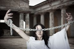 Restless Ghost. Pretty girl with arms in chains on a cemetery stock images