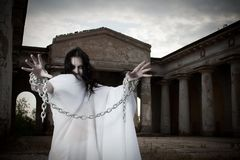 Restless ghost. Pretty gorhic girl with arms in chains posing on an old cemetery royalty free stock image