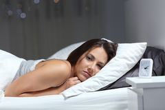 Restless girl suffering insomnia looking at you. In the bed in the night stock photos