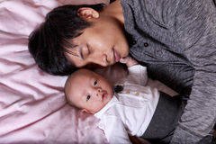 Restless infant baby boy with his sleeping father Stock Photography