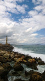 Restless rough sea with lots of waves and a famous lighthouse in city of Chania Crete, Greece Stock Photos