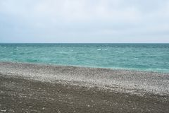 Restless sea before the rain with sandy beach. Seascape stock photography