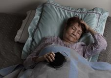 Restless senior woman holding alarm clock upside down during nighttime while in bed. Restless senior woman holding alarm clock face down during nighttime royalty free stock image