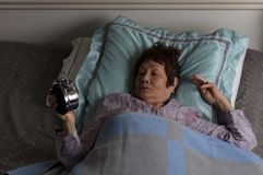Restless senior woman looking at alarm clock during nighttime while in bed. Restless senior woman staring at alarm clock during nighttime stock image