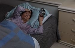 Restless senior woman with migraine during nighttime while in be. Restless senior woman holding her forehead and alarm clock during nighttime stock images