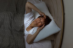 Restless senior woman staring at ceiling during nighttime while Royalty Free Stock Photography