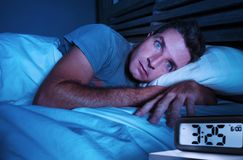 Restless worried young attractive man awake at night lying on be. D sleepless with eyes wide opened suffering insomnia sleeping disorder depressed and sad in stock images