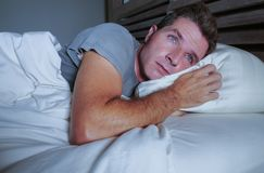Restless worried young attractive man awake at night lying on bed sleepless with eyes wide opened suffering insomnia sleeping diso. Rder depressed and sad in stock image