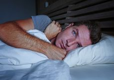 Restless worried young attractive man awake at night lying on bed sleepless with eyes wide opened suffering insomnia sleeping diso. Rder depressed and sad in royalty free stock photos