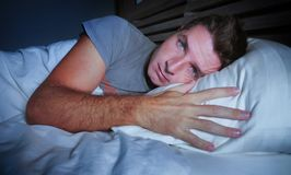 Restless worried young attractive man awake at night lying on bed sleepless with eyes wide opened suffering insomnia sleeping diso. Rder depressed and sad in royalty free stock images