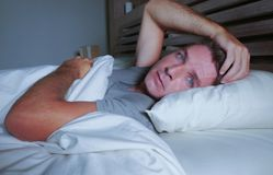 Restless worried young attractive man awake at night lying on bed sleepless with eyes wide opened suffering insomnia sleeping diso. Rder depressed and sad in stock photo