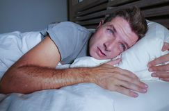Restless worried young attractive man awake at night lying on bed sleepless with eyes wide opened suffering insomnia sleeping diso. Rder depressed and sad in stock photos