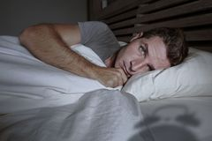 Restless worried young attractive man awake at night lying on bed sleepless having eyes opened depressed suffering insomnia sleepi. Restless and worried young stock images