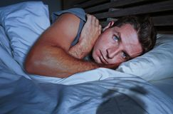 Restless worried young attractive man awake at night lying on bed sleepless having eyes opened depressed suffering insomnia sleepi. Restless and worried young royalty free stock photography