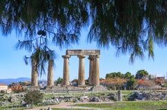 Restliche Spalten des Tempels von Apollo in altem Korinth mit Bergen und im Dorf im Hintergrund und in der Ansicht gestaltet durc lizenzfreies stockfoto