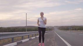 Resto activo y paisaje hermoso Muchacha en una camiseta blanca y zapatillas de deporte brillantes que corren en el camino en la p almacen de video