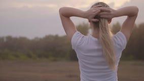 Resto activo y paisaje hermoso Una muchacha en una camiseta blanca contra el cielo en los rayos del sol poniente almacen de metraje de vídeo