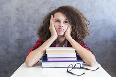 Resto adolescente de la muchacha del pelo rizado del aprendizaje en los libros Fotos de archivo libres de regalías