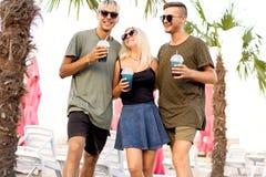 Resto alegre da empresa de três amigos em uma praia tropical e em cocktail da bebida; muito; conceito do compartimento fotografia de stock royalty free