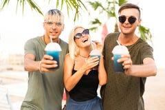 Resto alegre de la compañía de tres amigos en una playa y un drin tropicales imágenes de archivo libres de regalías