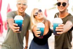 Resto alegre de la compañía de tres amigos en una playa y un drin tropicales fotos de archivo