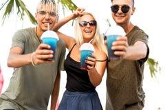 Resto alegre de la compañía de tres amigos en una playa y un drin tropicales imagen de archivo libre de regalías