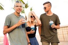 Resto alegre de la compañía de tres amigos en una playa y un drin tropicales imagenes de archivo
