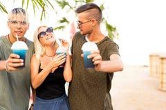 Resto alegre de la compañía de tres amigos en una playa y un drin tropicales fotografía de archivo