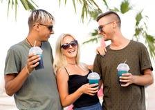 Resto alegre de la compañía de tres amigos en una playa y un drin tropicales fotos de archivo libres de regalías