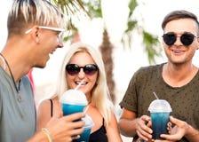 Resto alegre de la compañía de tres amigos en una playa y un drin tropicales fotografía de archivo libre de regalías