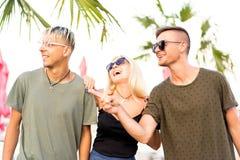 Resto alegre de la compañía de tres amigos en una playa y un drin tropicales foto de archivo